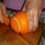 Tagliare e conservare da parte il cappello dell'arancia.