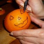 Disegnate occhi e bocca monodentata sull'arancia.